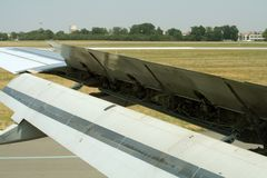 Air brakes. Airplane wing at landing with extended speed brakes Stock Photos