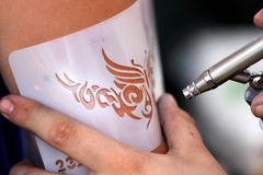 Air brush tattoo. Creating an air brush tattoo on a young girls arm royalty free stock photography