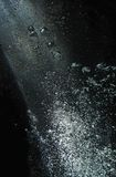 Air Bubbles Rising In Shaft Of Light Against Black Stock Image