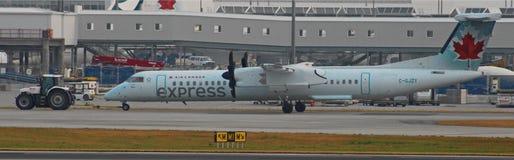 Air Canada-Streepje 8 wordt door een Tractor wordt gesleept die stock afbeeldingen