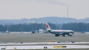 Air China acepilla en pista en el aeropuerto de Munich, Alemania, invierno con nieve almacen de metraje de vídeo