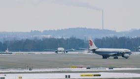 Air China acepilla en pista en el aeropuerto de Munich, Alemania, invierno con nieve almacen de video