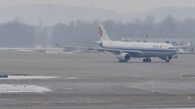 Air China Airbus A330-300 B-5957 que lleva en taxi en el aeropuerto de Munich, nieve