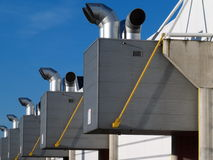 Air and climate treatment installations. Air and climate installations on an industrial building against a blue sky Royalty Free Stock Photo