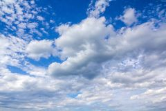 Air clouds soar in a bright blue sky stock images
