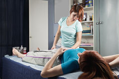Air compression massage. Masseuse looking at redhead women at air compression massage procedure purposed for lymphatic drainage improvement royalty free stock image