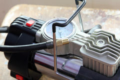 Air compressor. Car air compressor for pumping automobile tires on wooden background royalty free stock images