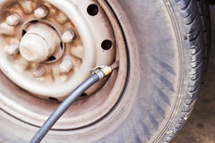 Air compressor tube on tire Royalty Free Stock Photos