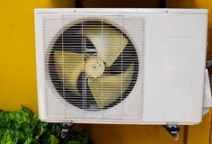 Air compressor on yellow wall. Closeup royalty free stock photography