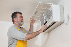 Air condition examine or install. Electrician examine or install air condition device in a room Royalty Free Stock Photography