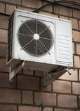 Air Conditioner. Air conditioning heat pump mounted on brick wall Royalty Free Stock Image