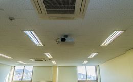 Air conditioner and beam projector on the ceiling. Old air conditioner and beam projector on the ceiling white tiled ceiling of classroom with bright sunlight Royalty Free Stock Photo