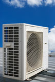 Air conditioner and blue sky. Air conditioner on a metal roof with blue sky in the background Stock Image