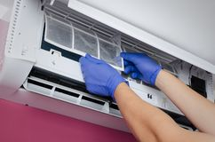 Air conditioner cleaning. Man checks the filter. Stock Images