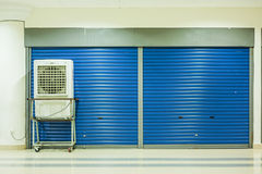 Air conditioner and closed doors. A mobile air conditioner in front of a closed shop lot Royalty Free Stock Photo
