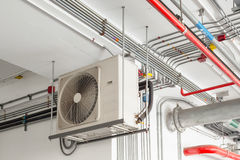 Air conditioner compressor installed and hanging on ceiling wall Royalty Free Stock Image