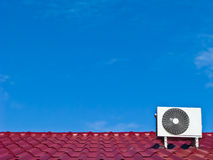 Air conditioner compressor on the red roof. Air conditioner's  compressor on the red roof with blue sky background Stock Images