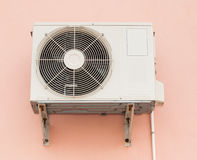 Air Conditioner Compressor Unit on Orange Wall Stock Images