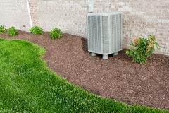 Air conditioner condenser unit standing outdoors Royalty Free Stock Photos