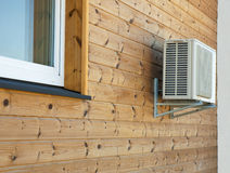 Air conditioner condenser on the wooden wall of boards. Air conditioner condenser on the wooden wall of boards exterior Stock Photos
