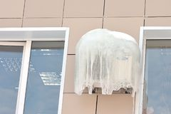 Air conditioner covered with frozen ice and icicles. Air conditioner covered with frozen ice and icicles on the wall between two windows. Concept of air Royalty Free Stock Photography