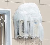 Air conditioner covered with frozen ice and icicles. Near the window. Air conditioner covered with frozen ice and icicles on the wall between two windows Stock Photography