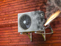 Air conditioner on fire. Overloaded electrical circuit causing electrical short and fire Stock Photos