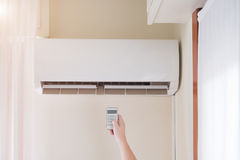 Air conditioner and hand with temperature remote control Stock Photo