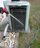 Air Conditioner Heat Pump Maintenance. Man spraying insect repellant on evaporator coils to prevent nesting and feeding ants from damaging the contactor of air Royalty Free Stock Images