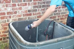 Air conditioner maintenance, compressor condenser coil. Compressor condenser coil outside of an air conditioner being cleaning by a technician and homeowner stock photos