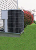 Air Conditioning. Residential Heating and Air Conditioning outdoor unit outside family house with green lawn Royalty Free Stock Photos