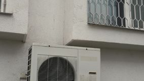 Air conditioner outside unit near apartment window. Air conditioner unit outside of the building near apartment windows stock video