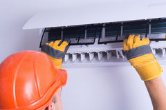 Air conditioner. Placing back clean filter into air conditioner stock photo