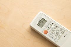 Air conditioner remote control on wood floor.  Royalty Free Stock Photography