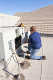 Air Conditioner Repair. Man accessing unit on rooftop by removing panel Stock Photos