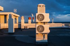 Air conditioner units on a roof of house. Blue sky and clouds in the background Stock Image