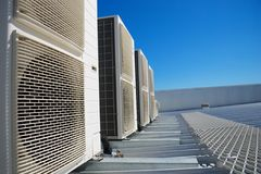 Air conditioner units. On the roof of an industrial building. Blue sky in the background. No people. Copy space Royalty Free Stock Photo