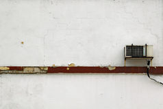 Air conditioner on white wall. A view of an old window air conditioning unit mounted on a white building exterior wall. Urban setting Royalty Free Stock Photo