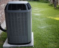 Air conditioner. And working sprinklers on backyard Royalty Free Stock Photography