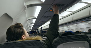 Air conditioning in aircraft. FRANKFURT, GERMANY - CIRCA 2015: Man turning on the air conditioner for fresh air an airplane stock video