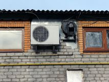 Air conditioning on a brick wall with small windows. White fan on a brick wall of an industrial building Stock Images