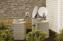 Air Conditioning Compressions and Satellite Dishes. Apartment air conditioning units with satellite dishes on top stock images