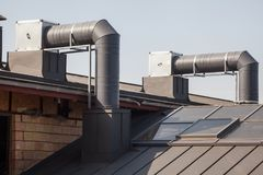 Air conditioning equipment atop a new metal roof of modern building. Air conditioning equipment atop a new metal roof of modern building Royalty Free Stock Image