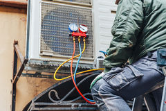 Air Conditioning Repair concept. Worker repairs air conditioner on the wall, Air Conditioning Repair concept royalty free stock photo