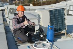Air Conditioning Repair. Young repairman on the roof fixing air conditioning system. Model is actual repairman / electrician Stock Photography