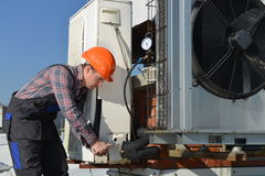 Air Conditioning Repair. Young repairman on the roof fixing air conditioning system. Model is actual repairman / electrician Royalty Free Stock Image