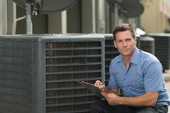 Air Conditioning Repairman. Thirtyish air conditioning repairman with clipboard Stock Photography