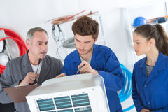 Air conditioning repairmen discussing problem with compressor unit. Air conditioning repairmen discussing the problem with a compressor unit Stock Image