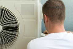 Air-conditioning system installation. Male technician installing air-conditioning system Royalty Free Stock Images