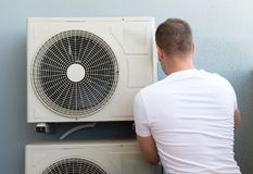 Air-conditioning system. Male technician installing air-conditioning system Stock Image